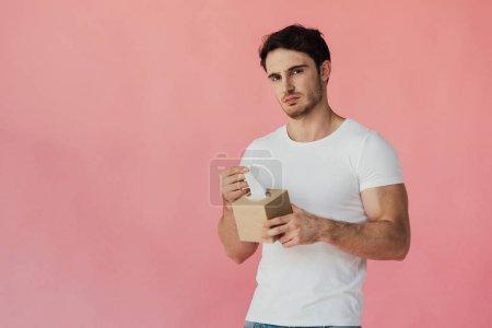 Photo pour Homme musclé mécontent en t-shirt blanc tenant des serviettes et regardant la caméra isolée sur rose - image libre de droit