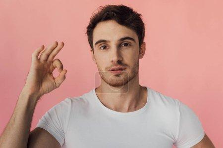 Photo pour Vue avant de l'homme musculaire dans le t-shirt blanc affichant le signe correct d'isolement sur le rose - image libre de droit