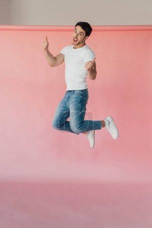 Foto de Hombre musculoso sonriente con camiseta blanca y jeans saltando y mostrando los pulgares hacia arriba en rosa - Imagen libre de derechos