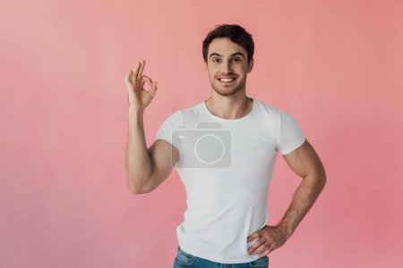 front view of smiling muscular man in white t-shirt showing okay sign isolated on pink