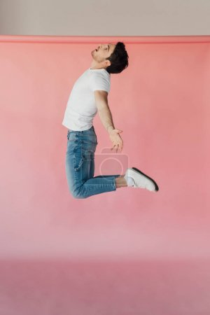muscular man in white t-shirt and jeans jumping on pink