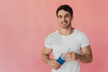 Photo for Muscular man in white t-shirt holding beverage isolated on pink - Royalty Free Image