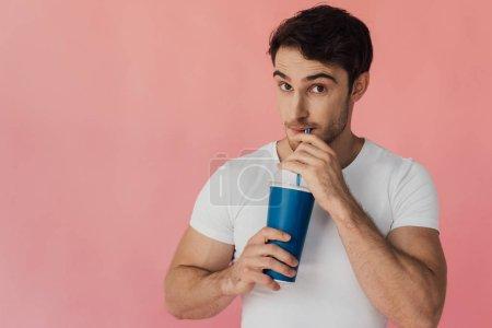 Photo pour Homme musculaire dans la boisson potable blanche de t-shirt d'isolement sur le rose - image libre de droit