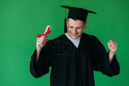 Photo pour Étudiant de sourire dans le diplôme de fixation de chapeau académique avec le ruban rouge et montrant le geste de oui isolé sur le vert - image libre de droit