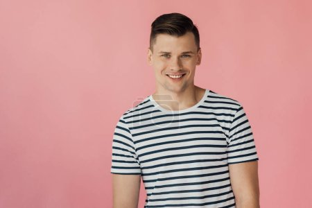 front view of handsome smiling man in striped t-shirt looking at camera isolated on pink