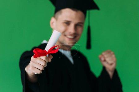 Photo pour Foyer sélectif de sourire étudiant en casquette académique titulaire d'un diplôme avec ruban rouge et montrant oui geste isolé sur vert - image libre de droit