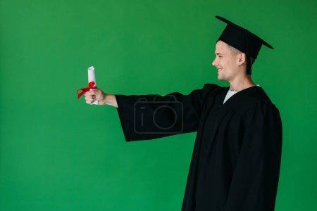 Photo pour Vue de côté de l'étudiant de sourire dans le diplôme de fixation de chapeau académique avec le ruban rouge d'isolement sur le vert - image libre de droit