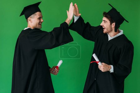Photo for Two happy students in academic caps holding diplomas and showing high five sign isolated on green - Royalty Free Image