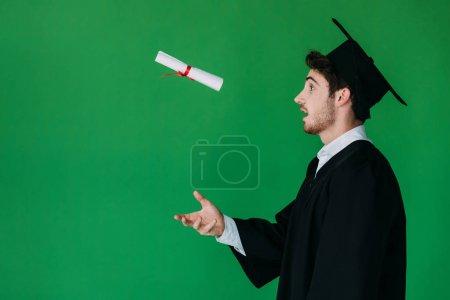 Photo pour Vue de côté de l'étudiant étonné dans le chapeau académique vomissant le diplôme avec le ruban rouge d'isolement sur le vert - image libre de droit