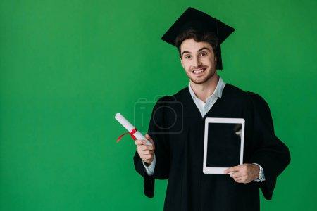 Photo pour Étudiant de sourire dans le diplôme de fixation de chapeau académique avec le ruban rouge et la tablette numérique avec l'écran blanc d'isolement sur le vert - image libre de droit