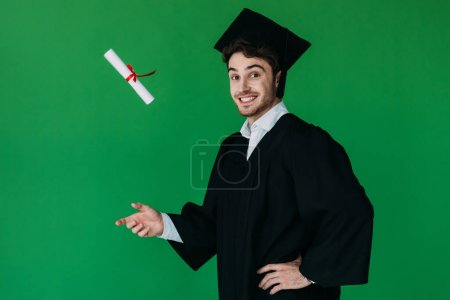 excited student in academic cap throwing up diploma with red ribbon isolated on green