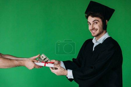 Photo pour Étudiant dans le diplôme de fixation de chapeau académique avec le ruban rouge et offrant le pot-de-vin isolé sur le vert - image libre de droit