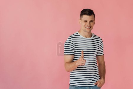 Photo for Smiling man in striped t-shirt standing with hand in pocket, blinking and showing thumb up isolated on pink - Royalty Free Image