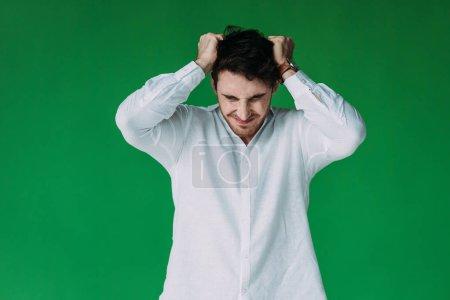 Photo pour Vue avant de l'homme stressé dans le cheveu blanc de contact de chemise d'isolement sur le vert - image libre de droit
