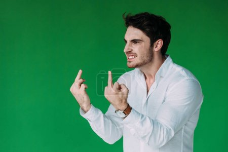 Photo for Angry man in white shirt showing middle fingers isolated on green - Royalty Free Image