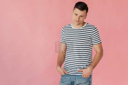 Foto de Hombre pensativo en camiseta a rayas de pie con las manos en los bolsillos aislados en rosa - Imagen libre de derechos