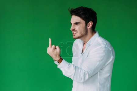 Photo for Angry man in white shirt looking away and showing middle finger isolated on green - Royalty Free Image
