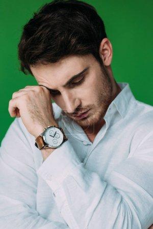 Photo pour Sérieux cher homme en chemise blanche et montre-bracelet toucher le visage avec la main isolé sur vert - image libre de droit