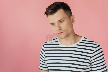 Photo for Pensive man in striped t-shirt looking away isolated on pink - Royalty Free Image