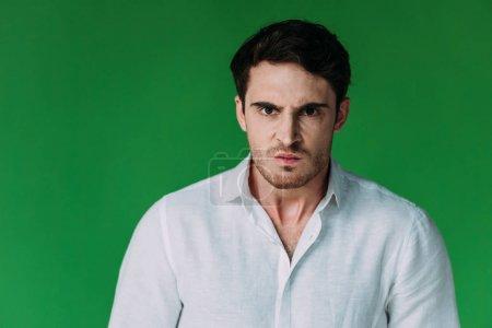 Foto de Vista frontal de hombre enojado en camisa blanca mirando la cámara aislada en verde - Imagen libre de derechos
