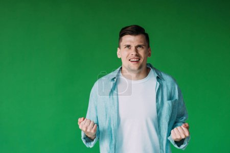 Photo for Front view of irritated young man in shirt holding fists up isolated on green - Royalty Free Image