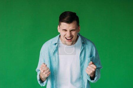 Photo pour Vue de face du jeune homme irrité en chemise tenant les poings isolés sur vert - image libre de droit