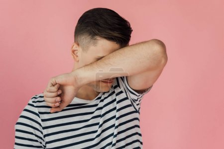 Photo for Young man in striped t-shirt wiping eyes with arm isolated on pink - Royalty Free Image