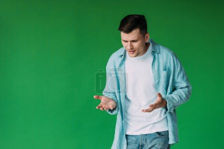 irritated young man in shirt gesturing isolated on green