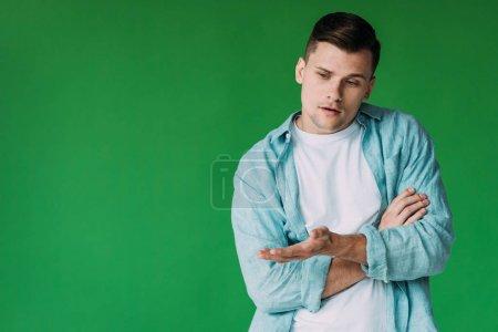 Photo pour Jeune homme pensif dans la chemise regardant vers le bas et faisant des gestes isolés sur le vert - image libre de droit