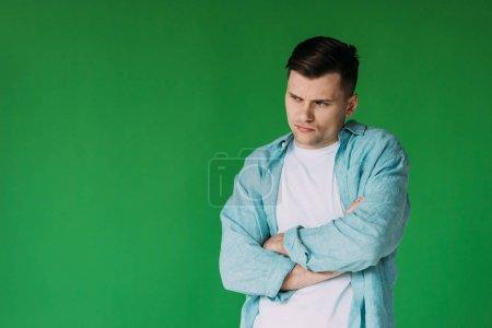 Photo pour Bouleversé jeune homme en chemise debout avec les bras croisés isolés sur vert - image libre de droit