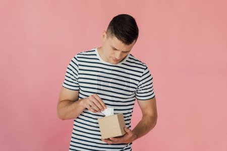 man in striped t-shirt holding napkins isolated on pink