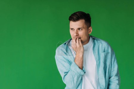 Photo for Worried young man in shirt biting fingers and looking away isolated on green - Royalty Free Image