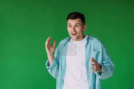 Photo for Excited young man in shirt gesturing isolated on green - Royalty Free Image