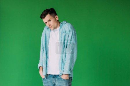 Photo pour Jeune homme confus dans la chemise restant avec des mains dans des poches et regardant la caméra d'isolement sur le vert - image libre de droit