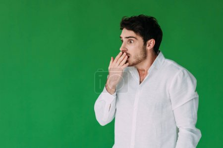 Photo for Scared young man in white shirt covering mouth with hand isolated on green - Royalty Free Image