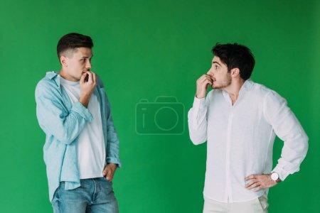 Foto de Dos hombres preocupados mordiendo los dedos y mirándose unos a otros aislados en verde - Imagen libre de derechos