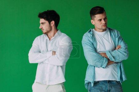 Foto de Dos hombres ofendidos en camisas de pie con los brazos cruzados aislados en verde - Imagen libre de derechos