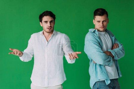Foto de Dos hombres ofendidos en camisas aisladas en verde - Imagen libre de derechos
