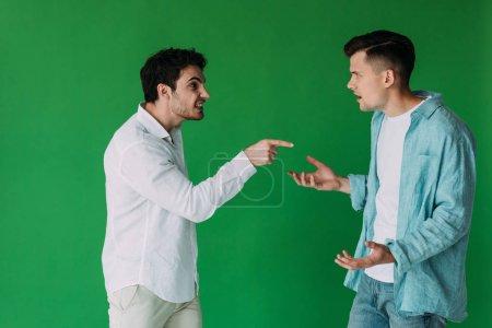 Foto de Dos hombres en camisas peleando y gritando el uno al otro aislado en verde - Imagen libre de derechos