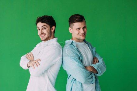 Photo pour Deux hommes de sourire restant avec les bras croisés et regardant la caméra d'isolement sur le vert - image libre de droit