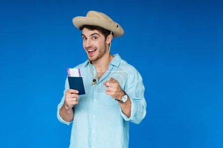 Photo pour Touriste souriant en chapeau de safari tenant passeport et billet d'avion et pointant du doigt la caméra isolée sur bleu - image libre de droit