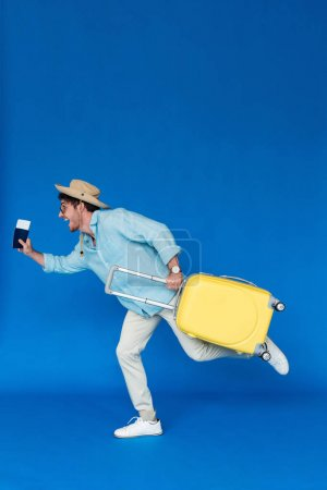 Photo for Full length view of hurrying traveler in safari hat and sunglasses holding yellow suitcase and running on blue - Royalty Free Image