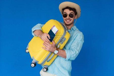 Photo pour Voyageur excité dans le chapeau de safari et les lunettes de soleil retenant la valise jaune et le passeport avec le billet d'avion d'isolement sur le bleu - image libre de droit