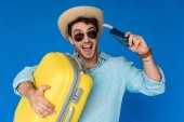 excited traveler in safari hat and sunglasses holding yellow suitcase and passport with air ticket isolated on blue