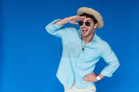 Photo for Excited tourist in safari hat and sunglasses laughing and looking in distance isolated on blue - Royalty Free Image