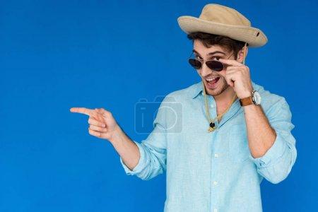 Photo pour Touriste excité dans le chapeau de safari et les lunettes de soleil riant et pointant avec le doigt isolé sur le bleu - image libre de droit