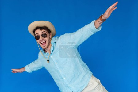 Photo pour Touriste excité dans le chapeau de safari et les lunettes de soleil riant et agitant des mains d'isolement sur le bleu - image libre de droit