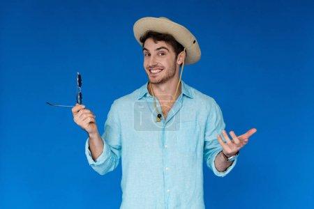 Photo pour Voyageur souriant en chapeau safari tenant des lunettes de soleil et regardant la caméra isolée sur bleu - image libre de droit