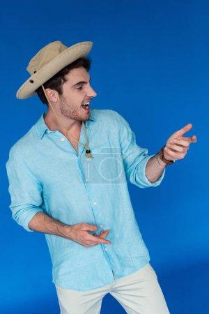 Photo pour Voyageur de sourire dans le chapeau de safari faisant des gestes et regardant loin isolé sur le bleu - image libre de droit