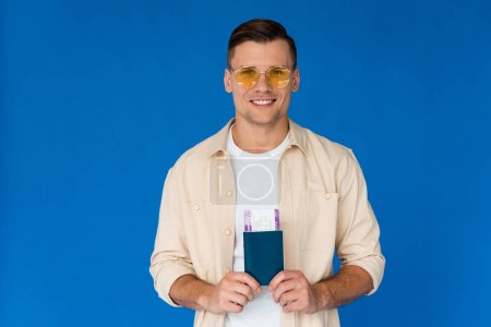 Foto de Vista frontal del viajero sonriente en gafas de sol con pasaporte con billete de avión aislado en azul - Imagen libre de derechos
